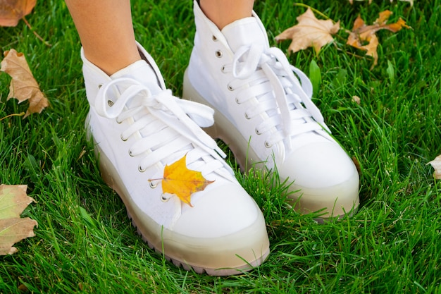 Nogi dziewczyny w białych butach w parku na zielonej trawie