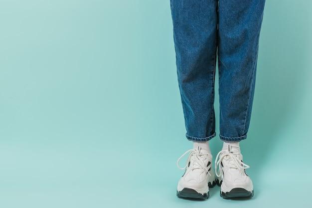 Nogi dziewczyny w białych skarpetkach, białych trampkach i dżinsach na niebiesko. stylowa młodzieżowa odzież i buty. miejsce na tekst.