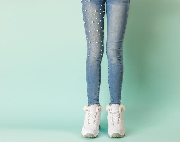Nogi dziewczyny w dżinsach z dżetów i ciepłych trampek na niebieskim tle.