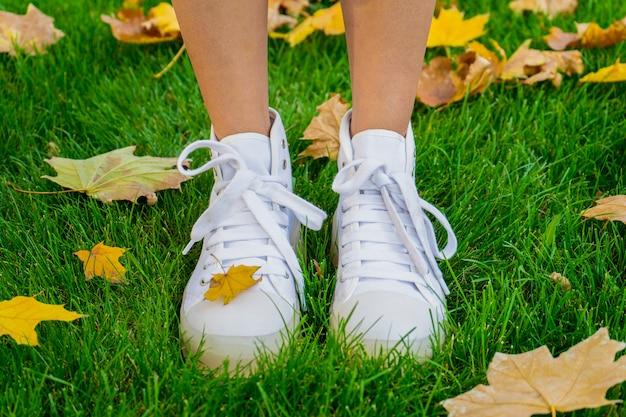 Nogi dziewczyny w jesień parku w białych butach na zielonym trawniku