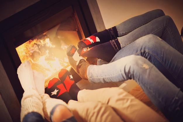 Nogi grupy przyjaciół odpoczywających nad kominkiem