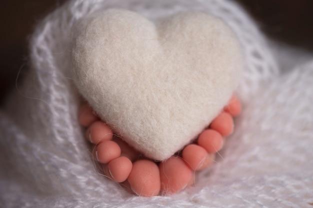 Nogi i palce noworodka w miękkim białym kocyku z serduszkiem. zdjęcie wysokiej jakości