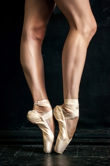Nogi i pointe baleriny z bliska na czarnej drewnianej podłodze