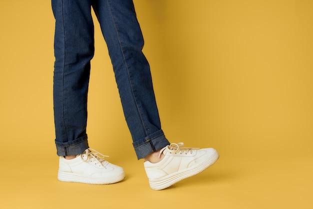 Nogi Jeansowe Modne Buty Białe Trampki żółta ściana Premium Zdjęcia