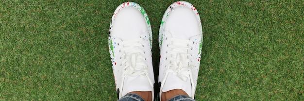 Nogi kobiet w niebieskich dżinsach i białych pięknych tenisówkach na zielonym trawniku