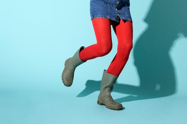 Nogi kobiety biegającej w kolorowych jaskrawoczerwonych leginsach i zielonych kaloszach