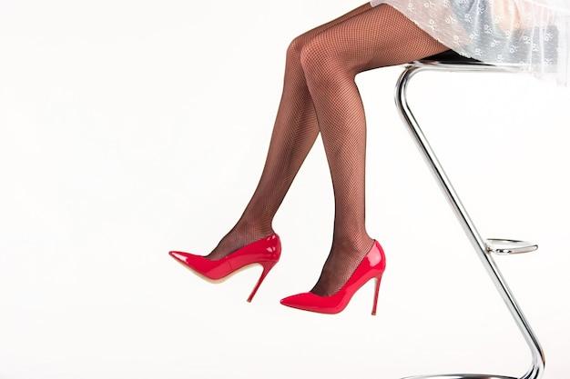 Nogi kobiety na wysokich obcasach. pani siedzi na krześle barowym. elegancja i kobiecość. nowa kolekcja obuwia.