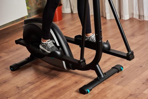 Nogi kobiety trenujące na orbitreku w salonie w domu