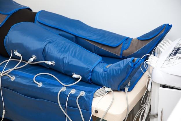 Nogi kobiety w specjalnej osłonie w salonie piękności. alternatywne leczenie ciała. pressoterapia przeciwtłuszczowa.