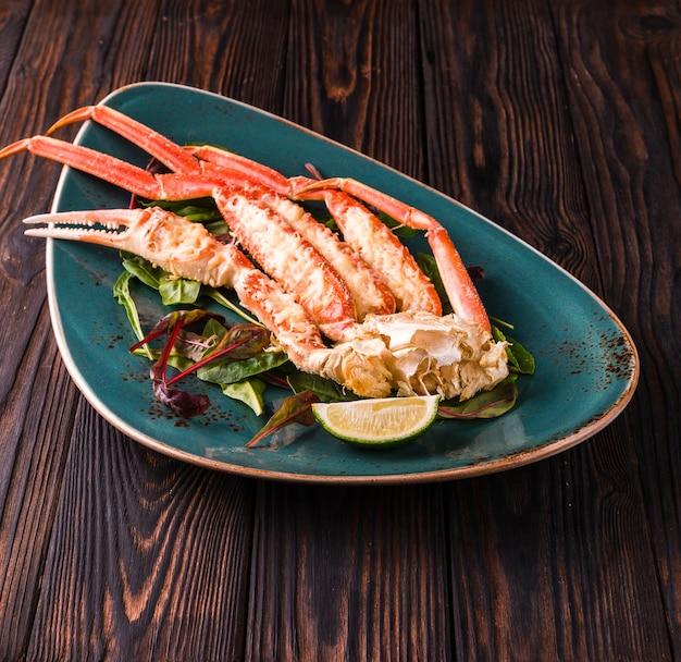 Nogi kraba z plasterkami świeżej cytryny w zielonym talerzu na ciemnym drewnianym stole.