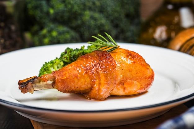 Nogi kurczaka z warzywami na drewnianym stole.