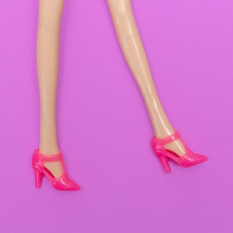 Nogi lalki w stylowych różowych butach na obcasie. moda minimalna płaska sztuka świecka