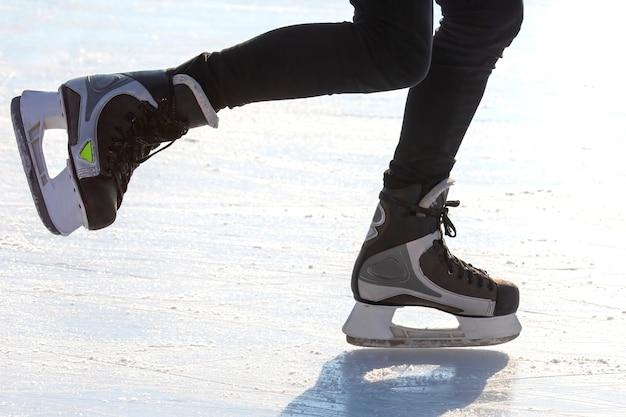 Nogi łyżwiarza na łyżwach na ulicznym lodowisku. sporty zimowe. hobby i aktywny wypoczynek w sporcie.
