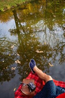 Nogi małej dziewczynki w pobliżu jeziora leżą na czerwonej kraciastej kraciastej kracie. piękne odbicie w wodzie, opadłe liście na wodzie. widok z góry