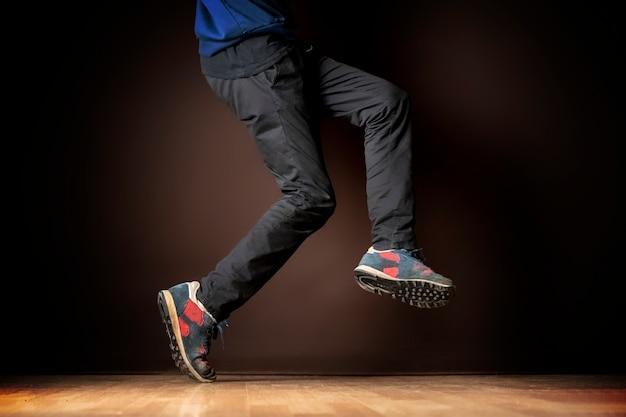 Nogi męskiej tancerki na ciemnym tle b