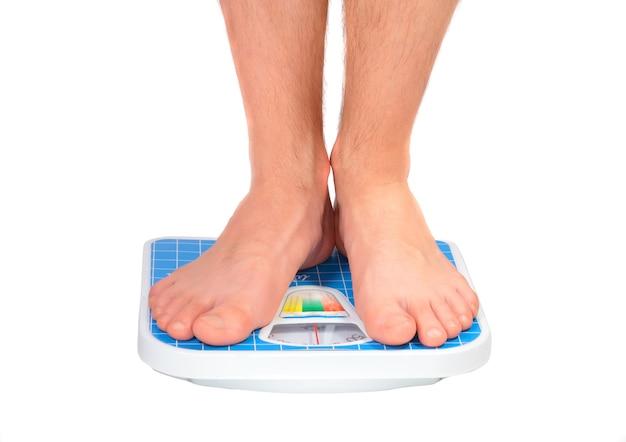 Nogi mężczyzny, które ważyły na wadze podłogowej. pojedynczo na białym