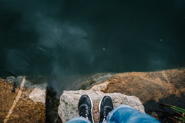 Nogi mężczyzny stoją na kamieniu przed jeziorem