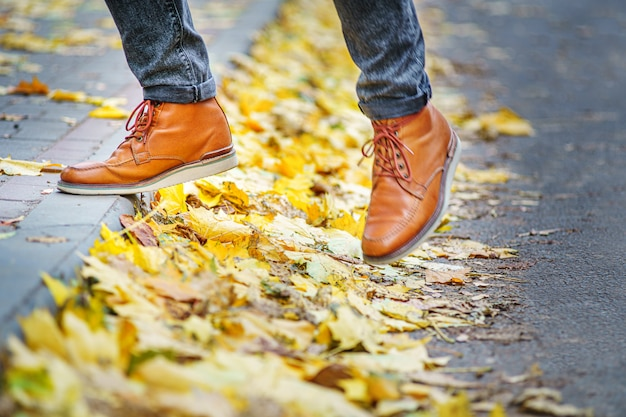 Nogi mężczyzny w brązowych butach idącego chodnikiem usłanym opadłymi liśćmi.