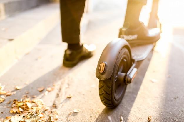 Nogi mężczyzny w stylowym stroju stoją na skuterze elektrycznym na ulicy
