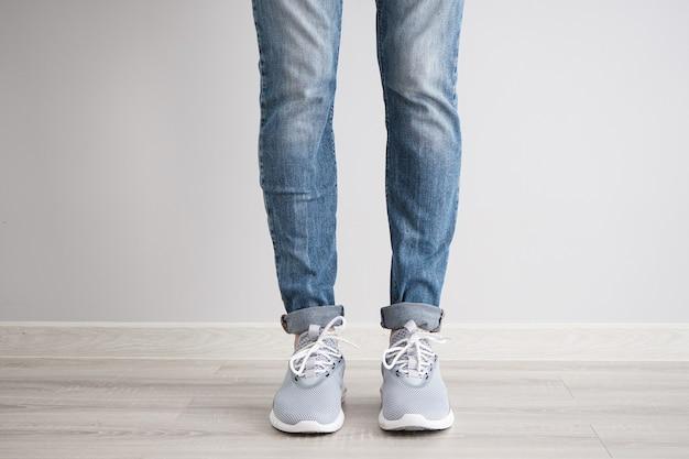 Nogi młodego mężczyzny w dżinsach i trampkach na szarej ścianie.