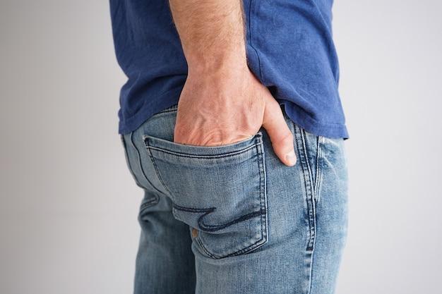 Nogi młodego mężczyzny w dżinsach z ręką w kieszeni na szarej ścianie.