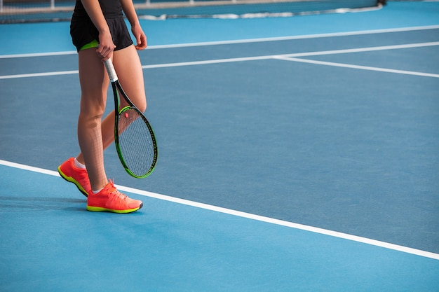 Nogi młodej dziewczyny w zamkniętym korcie tenisowym z piłką i rakietą