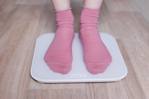 Nogi młodej kobiety mierzącej swoją wagę na nowoczesnej inteligentnej wadze.