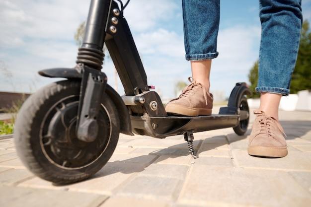 Nogi młodej kobiety w beżowych butach i niebieskich dżinsach stojących na skuterze elektrycznym na drodze w środowisku miejskim i zachmurzonym niebie