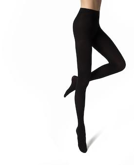 Nogi młodej kobiety w czarnych nylonowych rajstopach na białym tle