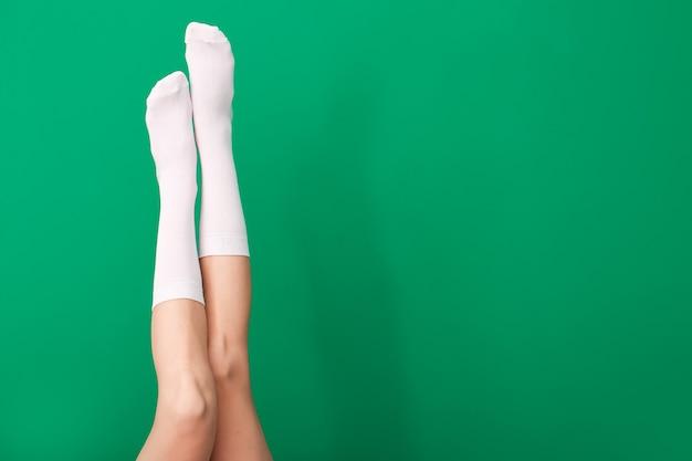 Nogi młodej kobiety w skarpetkach na kolorowej powierzchni