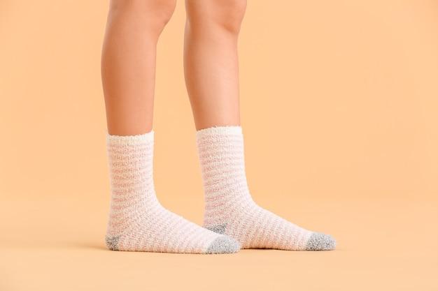 Nogi młodej kobiety w skarpetkach na kolorowym tle