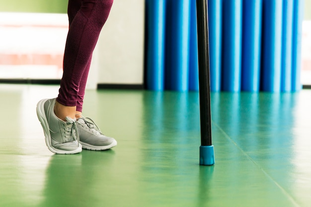 Nogi młodych dopasowanie kobiety robienie ćwiczeń z bodybar w siłowni