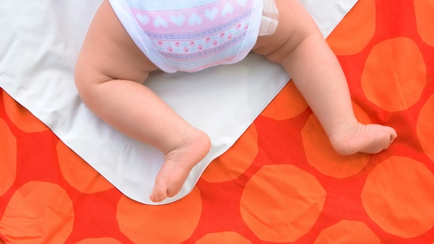 Nogi noworodka na kocu. bose stopy niemowlę dziewczynka, widok z tyłu.