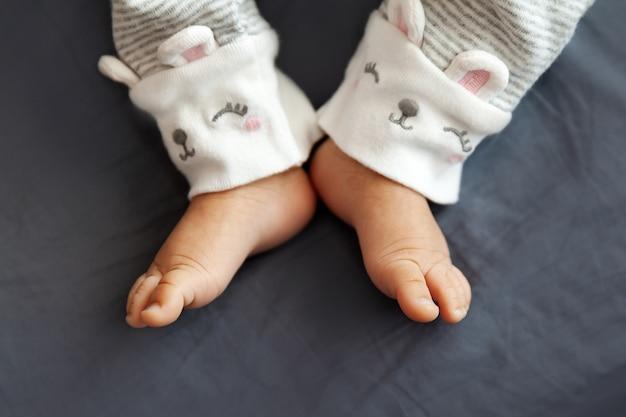 Nogi noworodka na łóżku w selektywnej ostrości, zbliżenie małych palców
