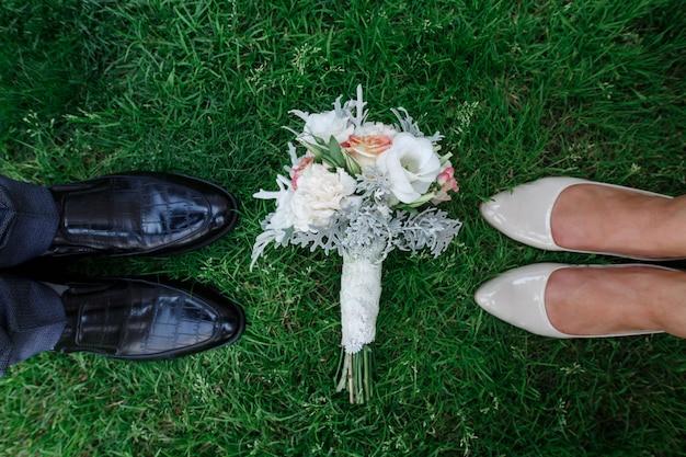 Nogi nowożeńców o charakterze w słoneczny dzień. stylowe obuwie panny młodej i pana młodego na zewnątrz. bukiet ślubny na zielonej trawie. stylowe buty damskie i męskie. dzień ślubu. szczegóły ślubu.