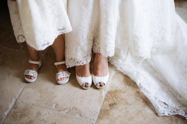 Nogi panny młodej w białych butach, a obok niej mała dziewczynka w sandałach