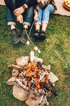 Nogi pary blisko ognia, która piecze pianki. koncepcja pikniku