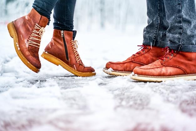 Nogi pary na zaśnieżonym chodniku w brązowych butach