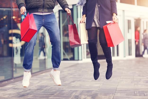 Nogi pary z torbami na zakupy po zakupach w mieście uśmiechnięte i przytulone