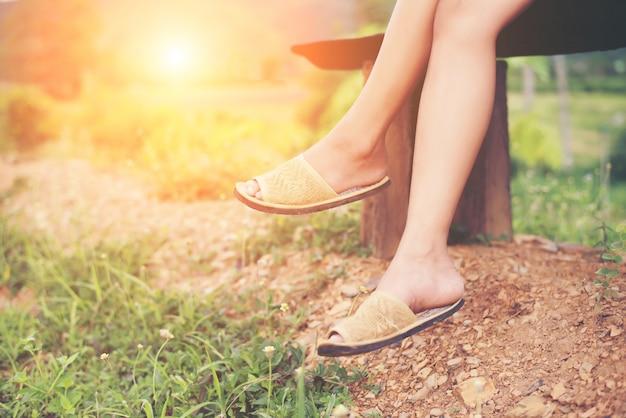Nogi pięknej kobiety siedzącej na ławce pośród kwiatów i