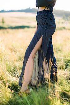 Nogi pięknej młodej damy w czarne modne spodnie, spacery w letnim zielonym polu