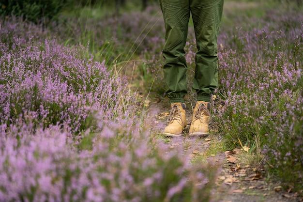 Nogi podróżnika na tle kwietnego pola w lesie