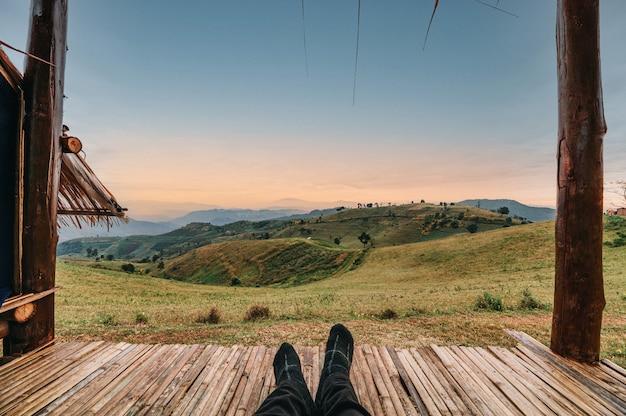 Nogi podróżnika relaksującego się w chacie na zielonym wzgórzu na wsi