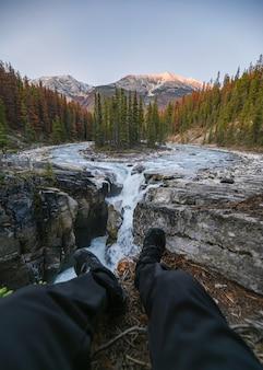 Nogi podróżnika siedzą rozciągające się nad wodospadem sunwapta w icefields parway w parku narodowym jasper w kanadzie