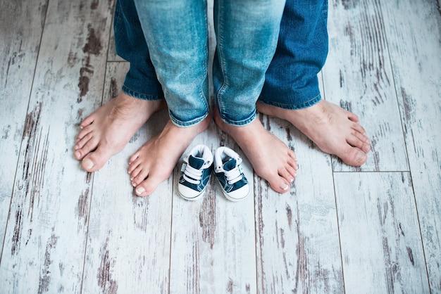 Nogi rodziców w dziecięcych trampkach czekam na dziecko