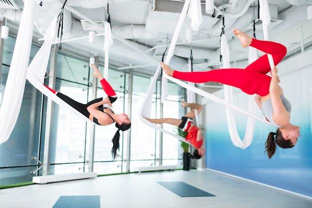 Nogi się rozciągają. aktywne i sprawne kobiety i mężczyźni rozciągające nogi podczas wykonywania jogi latania