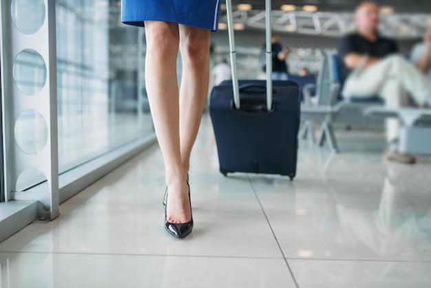 Nogi stewardessy i walizka w hali lotniska