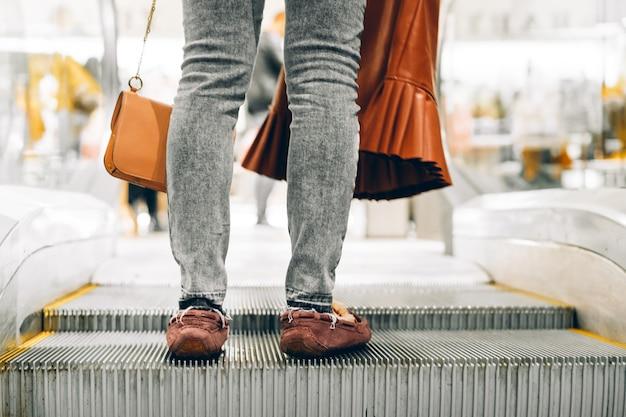 Nogi stojące na schodach centrum handlowego