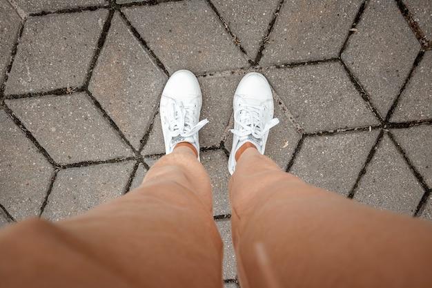Nogi w białych trampkach i beżowych spodniach widok z góry. selfie świetnie nadaje się do każdego zastosowania.