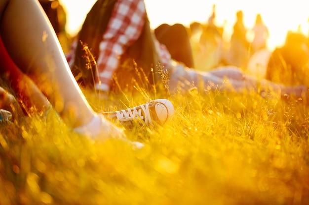 Nogi w butach sportowych lub trampkach w trawie. ludzie na wakacjach na ziemi